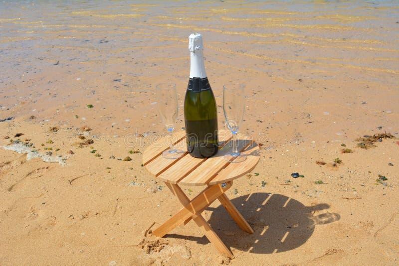 Dos vidrios de la isla de Champagne And Bottle In Paradise imagenes de archivo