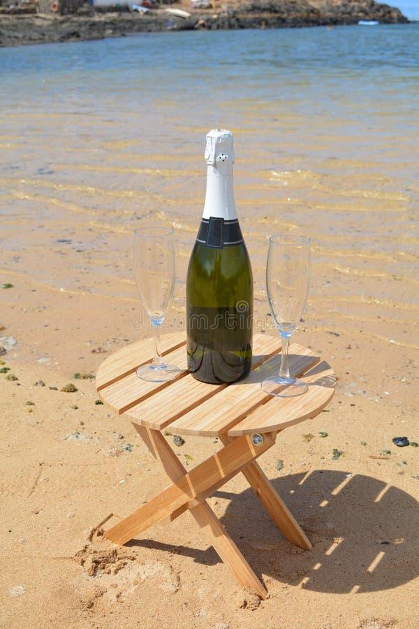 Dos vidrios de la isla de Champagne And Bottle In Paradise foto de archivo libre de regalías