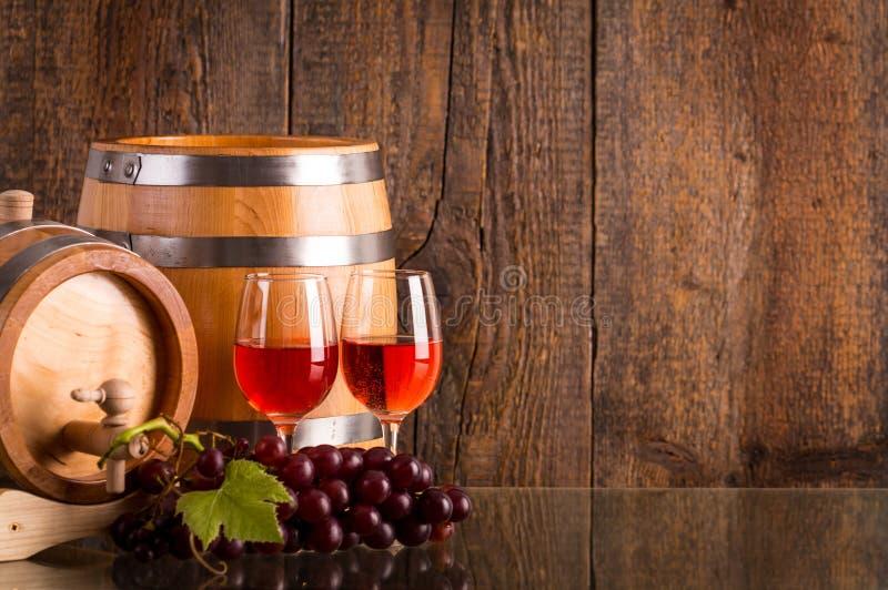 Dos vidrios de rosé wine con dos barriles y uvas imagenes de archivo