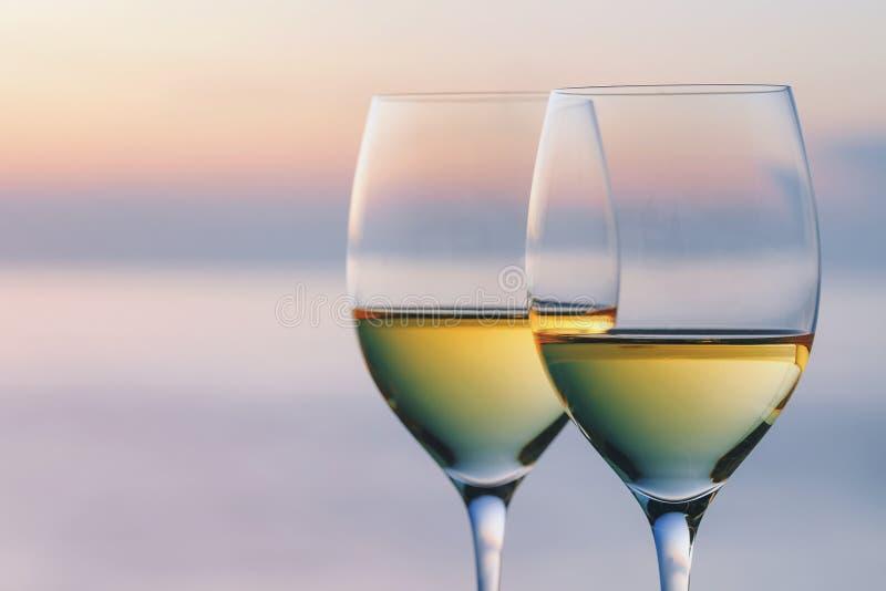 Dos vidrios de vino contra el contexto del sol poniente imagenes de archivo