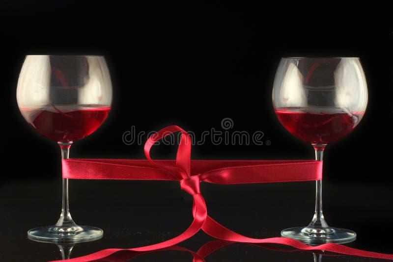 Dos vidrios de vino envueltos con un burocrático foto de archivo libre de regalías