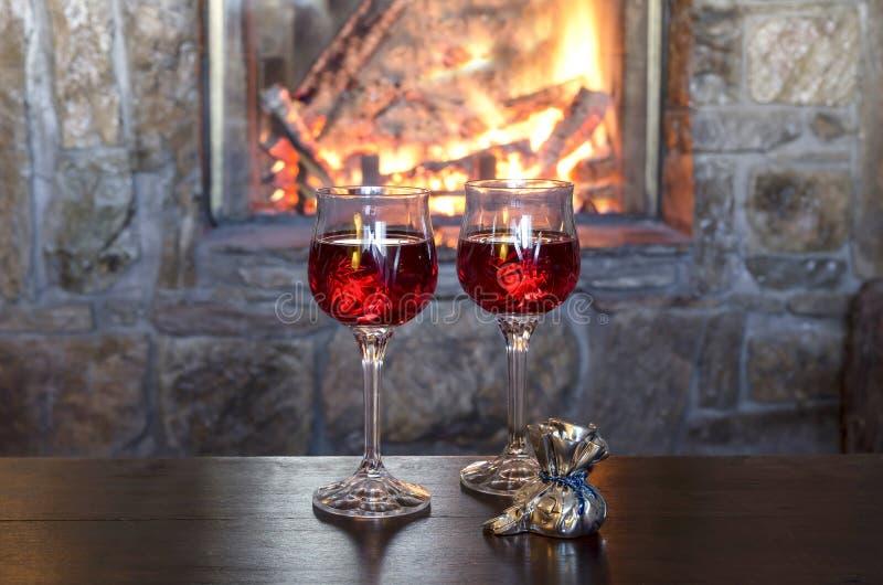 Dos vidrios de vino por la chimenea imagen de archivo