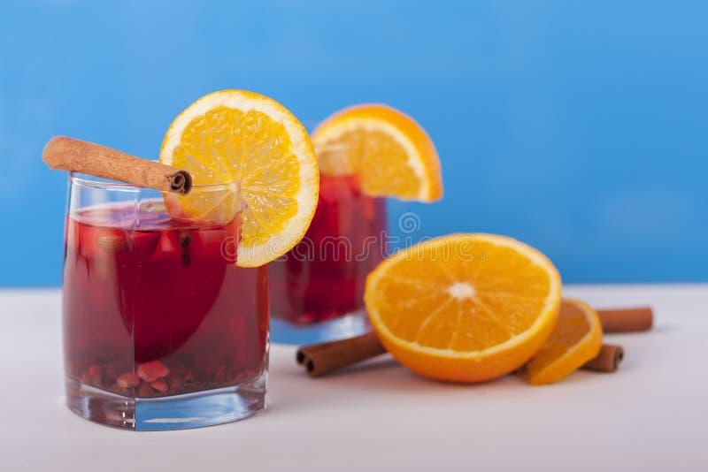 Dos vidrios de vino reflexionado sobre, adornados con los palillos de canela y la naranja fotos de archivo libres de regalías