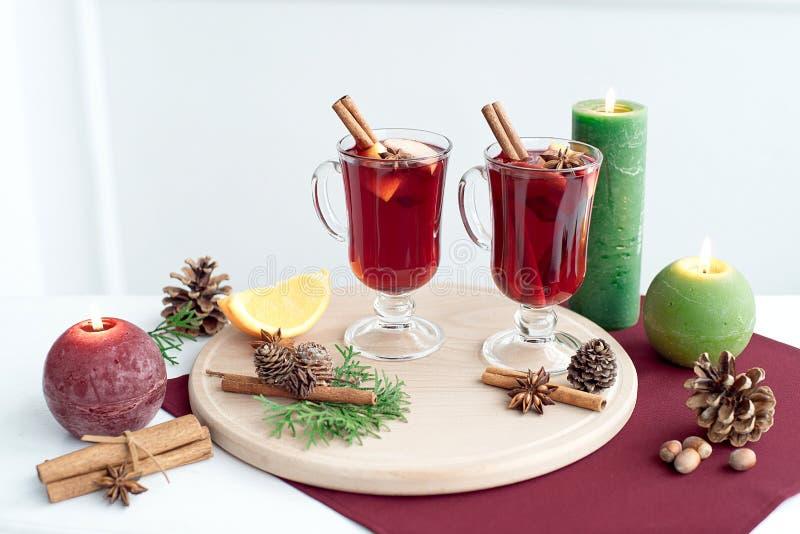 Dos vidrios de vino reflexionado sobre con los palillos de canela, de una rebanada seca de naranjas y de los conos, anís de estre fotografía de archivo