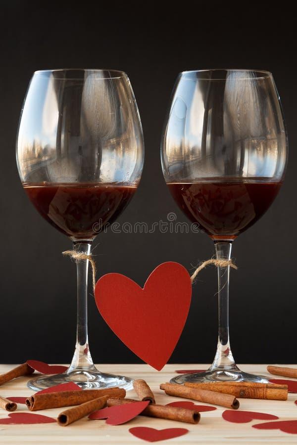 Dos vidrios de vino rojo atados con el corazón rojo fotografía de archivo libre de regalías
