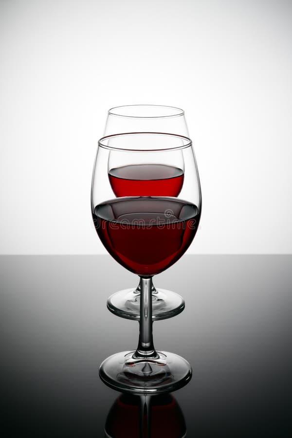 Dos vidrios de vino rojo con descensos y reflexiones en una tabla de cristal imagenes de archivo