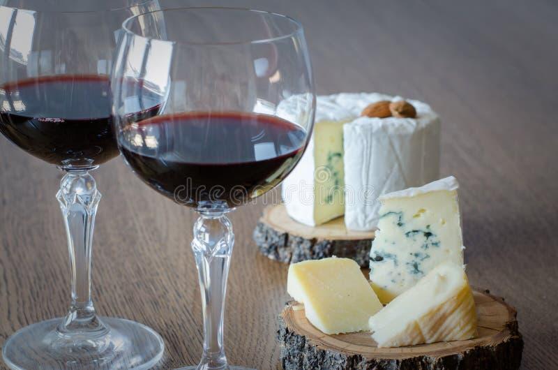 Dos vidrios de vino rojo con pocos pedazos de queso en el backgr de madera fotografía de archivo