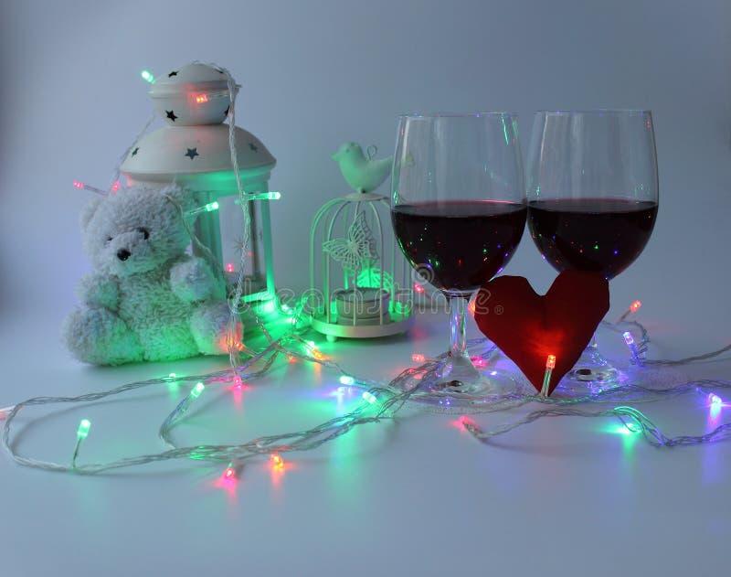 Dos vidrios de vino rojo, un corazón decorativo Un símbolo del amor Día del `s de la tarjeta del día de San Valentín imagen de archivo