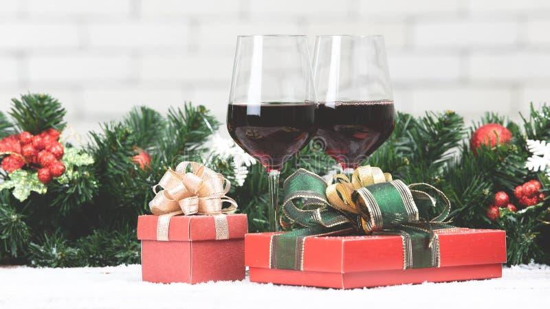 Dos vidrios de vino tinto fijados al lado de boxex rojo del regalo en la tabla nevosa p fotos de archivo libres de regalías