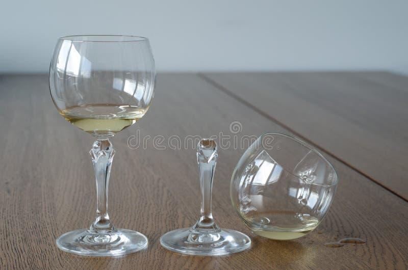 Dos vidrios de vino Una mitad vidrio roto lleno y otro medio fu imágenes de archivo libres de regalías