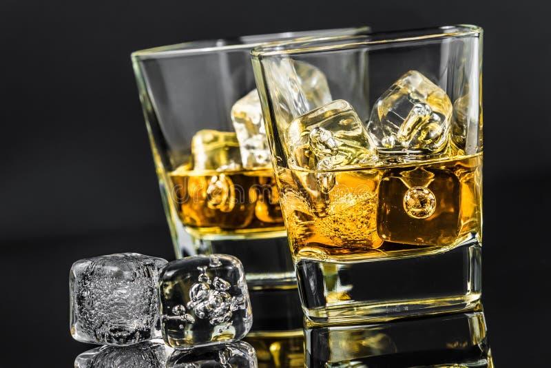 Dos vidrios de whisky cerca de los cubos de hielo en fondo oscuro imagen de archivo