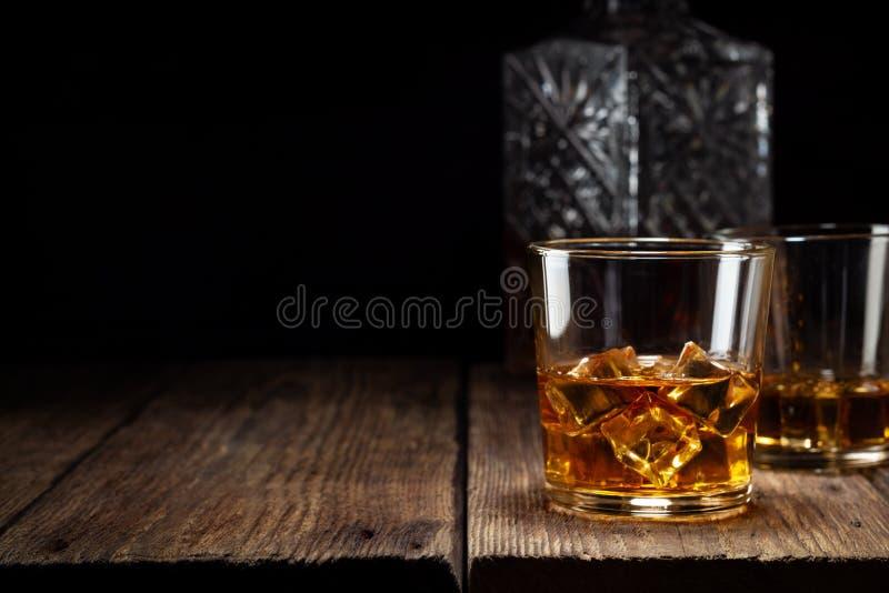 Dos vidrios de whisky con hielo y la jarra cristalina en la tabla de madera foto de archivo libre de regalías