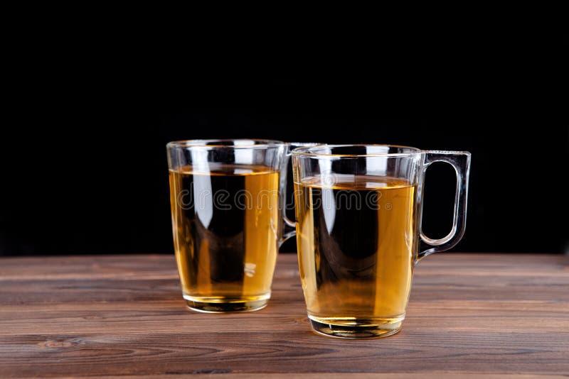 Dos vidrios de zumo de manzana en un fondo negro imagen de archivo libre de regalías