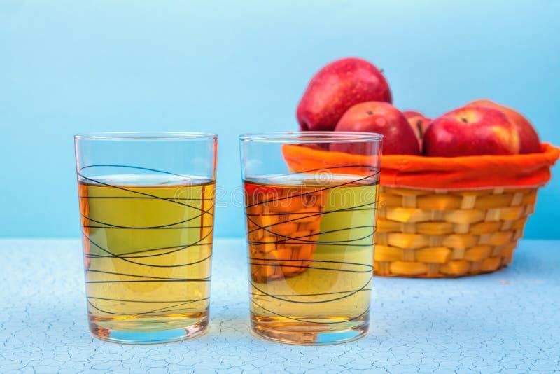Dos vidrios de zumo de manzana y de manzanas rojas en fondo de madera fotos de archivo