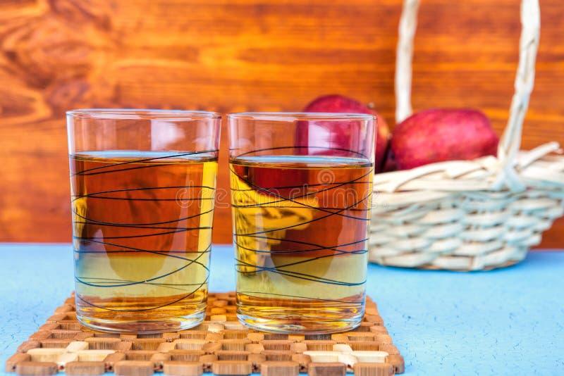 Dos vidrios de zumo de manzana y de manzanas rojas en fondo de madera imagenes de archivo