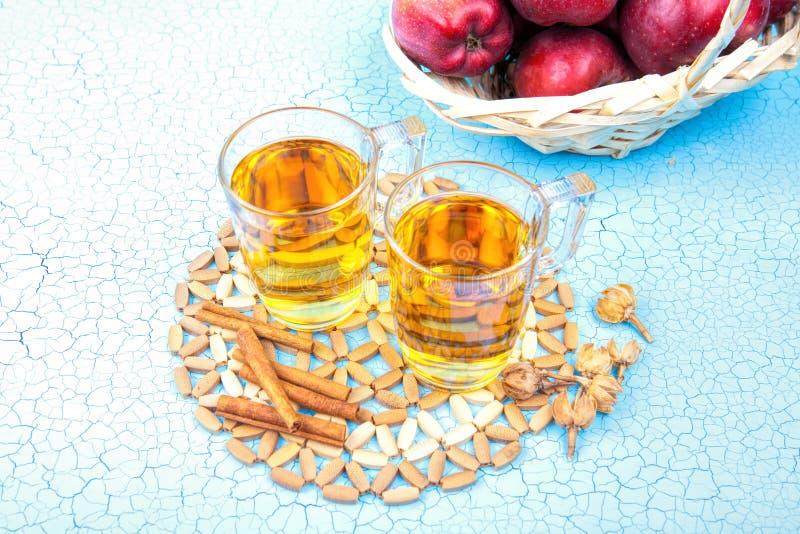 Dos vidrios de zumo de manzana y de manzanas rojas en fondo de madera imagen de archivo