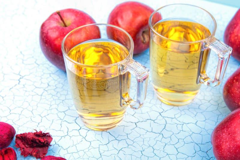 Dos vidrios de zumo de manzana y de manzanas rojas en fondo de madera fotografía de archivo