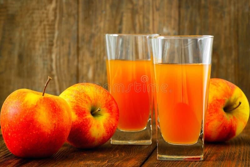 Dos vidrios de zumo y de las manzanas de manzana en de madera fotografía de archivo