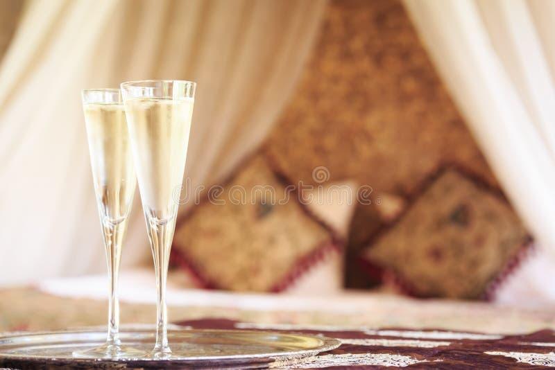 Dos vidrios del champán con el toldo oriental acuestan en el fondo fotos de archivo