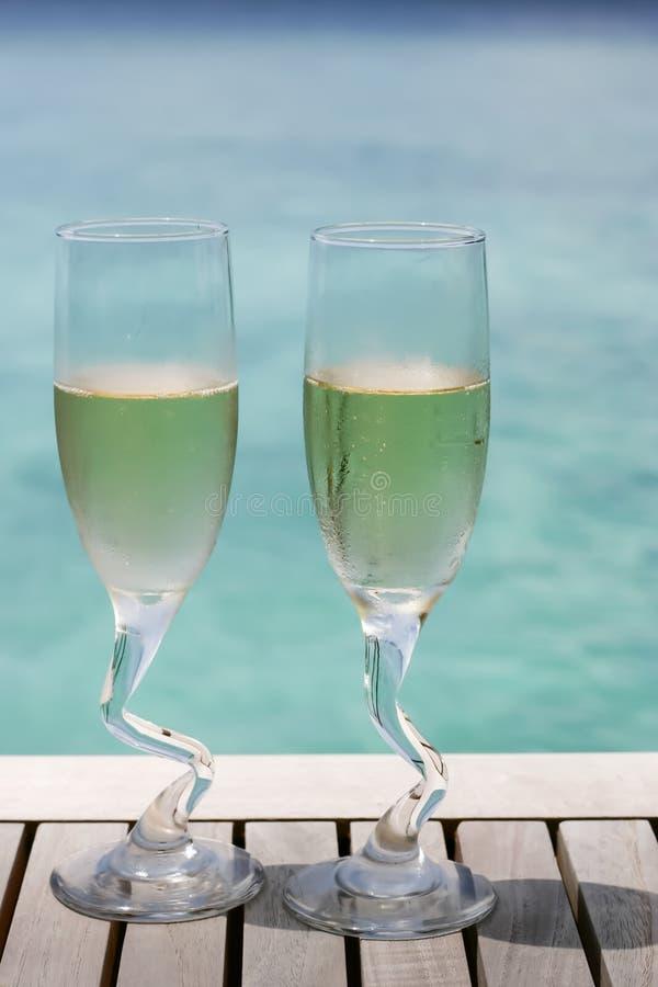 Dos vidrios del champán por el océano fotografía de archivo libre de regalías