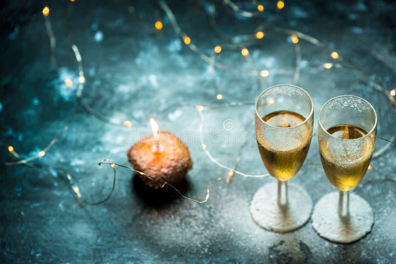 Dos vidrios del champán y del mollete con una vela en fondo oscuro, romántico, tranquilo fotografía de archivo