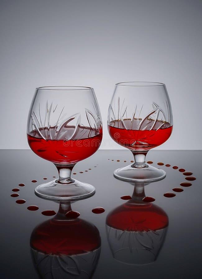 Dos vidrios del soporte del vino tinto en la superficie del espejo imagen de archivo