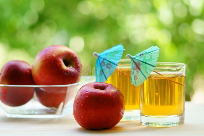 Dos vidrios del zumo de manzana con la manzana roja y de un cuenco con las manzanas rojas en él imagen de archivo