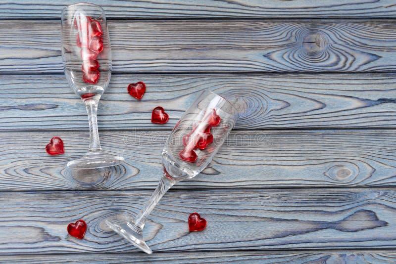 Dos vidrios, figuras rojas en la forma de un corazón en un fondo de madera Fecha romántica fotografía de archivo