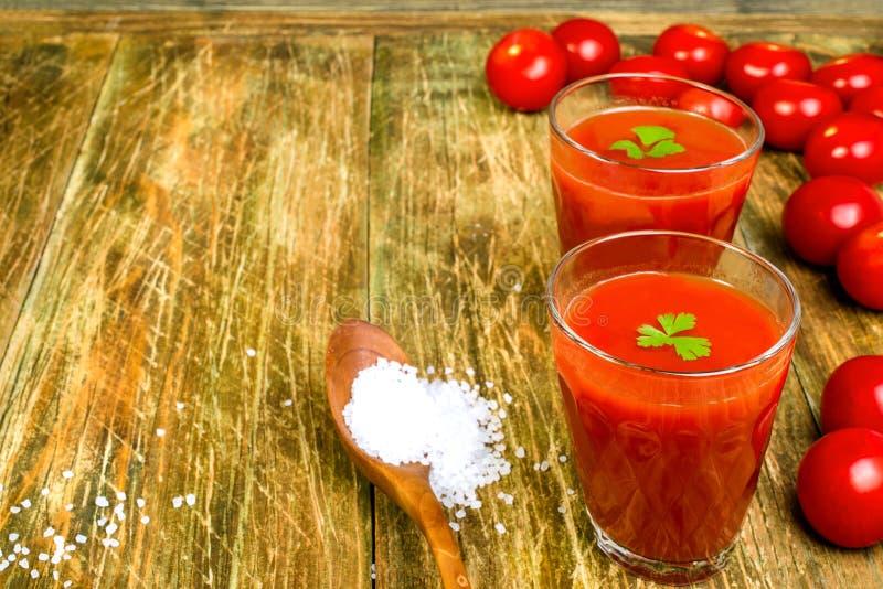 Dos vidrios llenos de jugo de tomate fresco, y tomatoesand s de madera imagenes de archivo