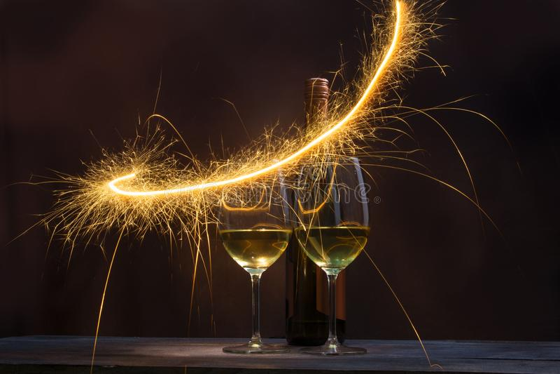 Dos vidrios que contienen el vino con las botellas de vino se adornan con los fuegos artificiales chispeantes fotos de archivo libres de regalías