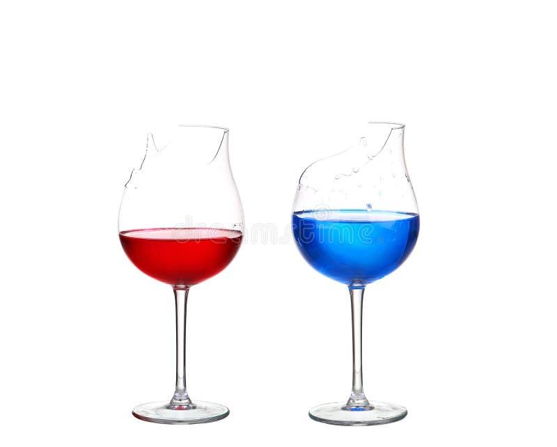 Dos vidrios quebrados con el cóctel rojo y azul en el aislante blanco foto de archivo