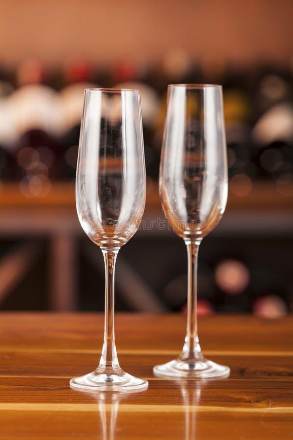 Dos vidrios vacíos en fondo con las botellas de vino foto de archivo