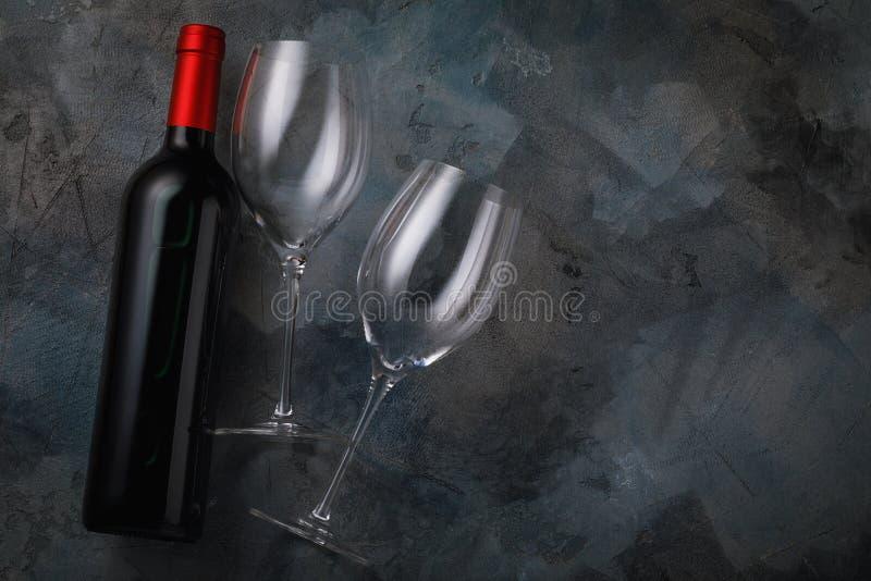 Dos vidrios vacíos y una botella de vino tinto en la tabla imagen de archivo
