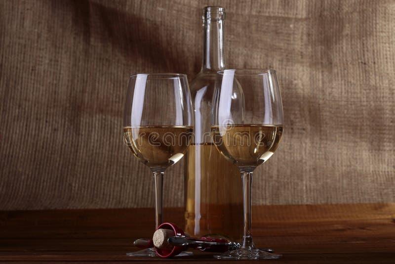 Dos vidrios y botellas de vino blanco fotografía de archivo libre de regalías
