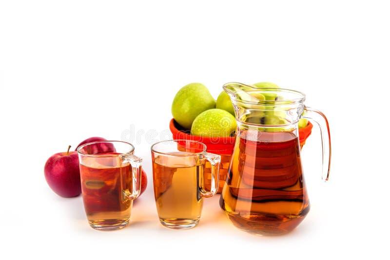 Dos vidrios y un jarro de zumo de manzana, aislado en el backgro blanco fotografía de archivo libre de regalías