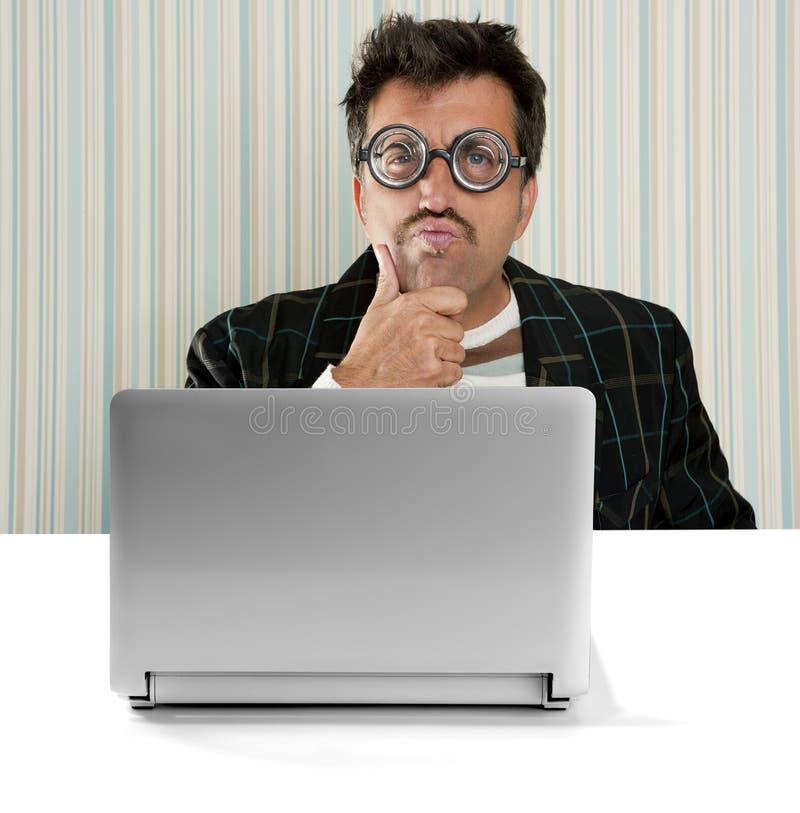 Dos vidros pensativos do homem do lerdo portátil parvo da expressão imagem de stock