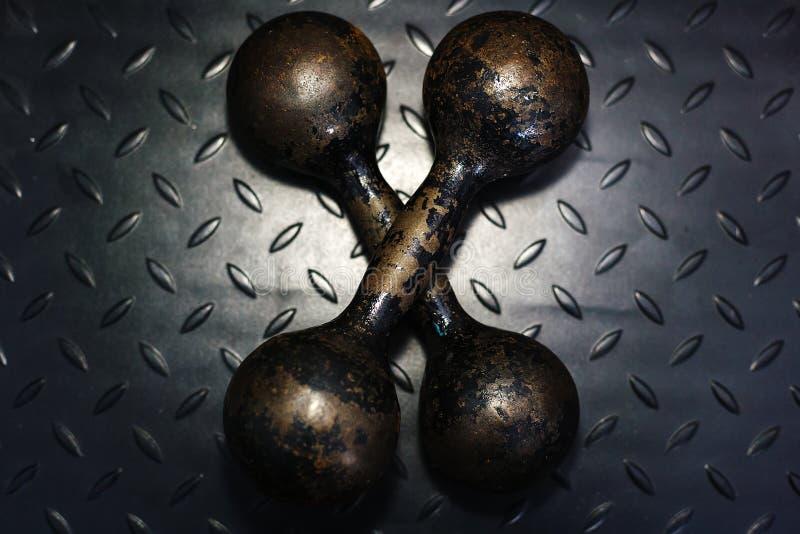 Dos viejas pesas de gimnasia del hierro del color negro en un fondo metálico negro fotografía de archivo libre de regalías