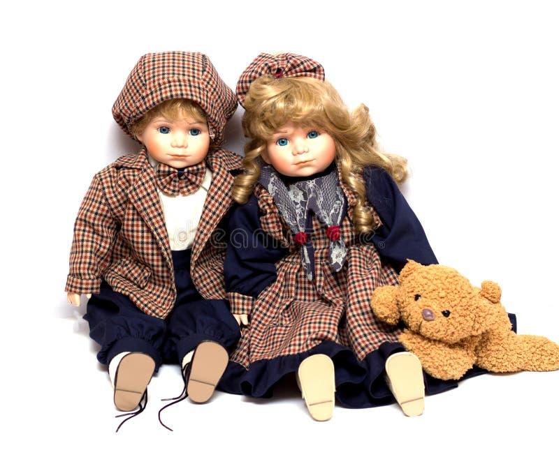 Dos viejos, muñecas de cerámica y un oso de peluche Muñeca vieja de la porcelana en el fondo blanco fotos de archivo