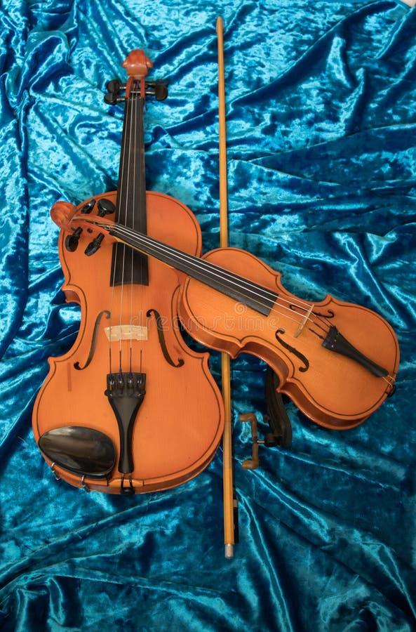 Dos violines de diversos tamaños en tela azul fotografía de archivo