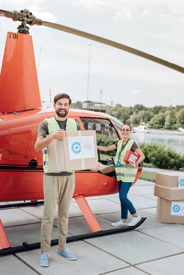 Dos voluntarios joviales que cargan casos fotografía de archivo