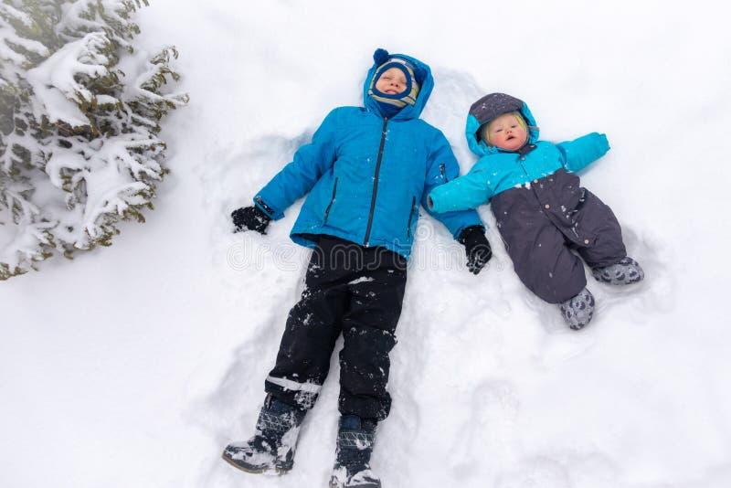 Dos 8 y 0 años de los muchachos, mentira en una nieve acumulada por la ventisca blanca limpia cerca de la picea fotografía de archivo libre de regalías