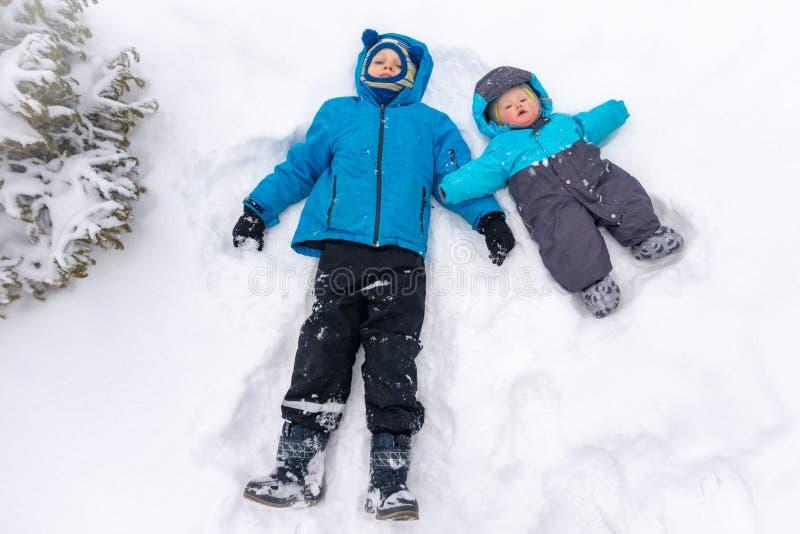 Dos 8 y 0 años de los muchachos, mentira en una nieve acumulada por la ventisca blanca limpia cerca de la picea imagen de archivo libre de regalías