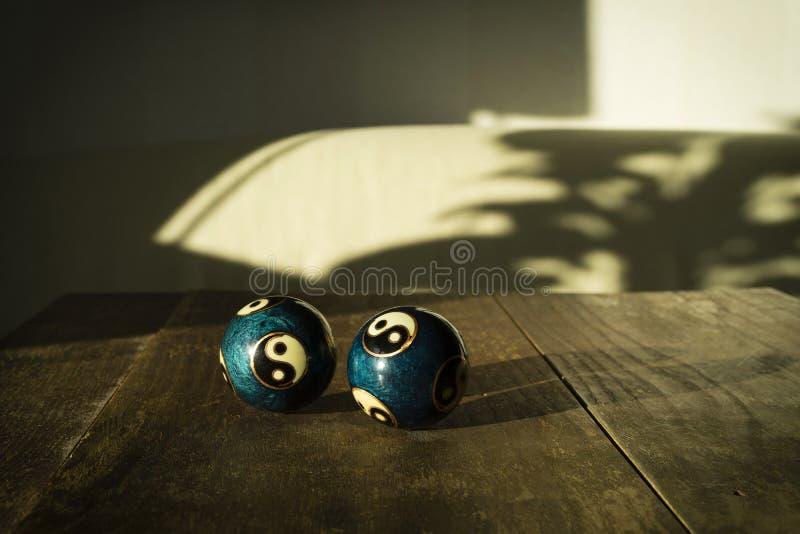 Dos yin y baodingballs hermosos de yang en la tabla de madera oscura en sol fotografía de archivo