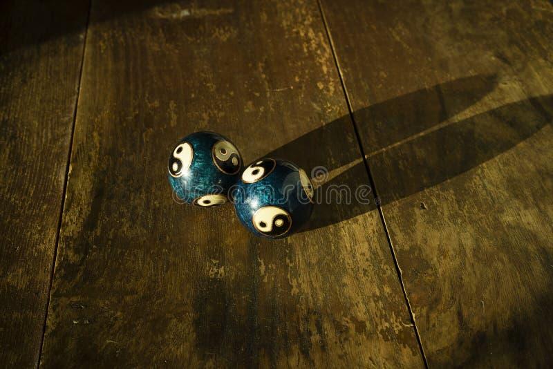 Dos yin y bolas hermosos de yang en la tabla de madera oscura en sol fotos de archivo