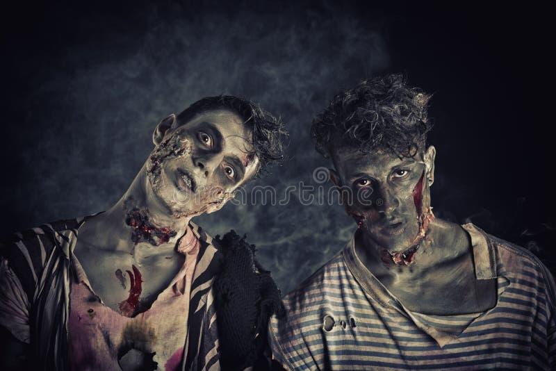 Dos zombis masculinos que se colocan en fondo ahumado negro foto de archivo libre de regalías