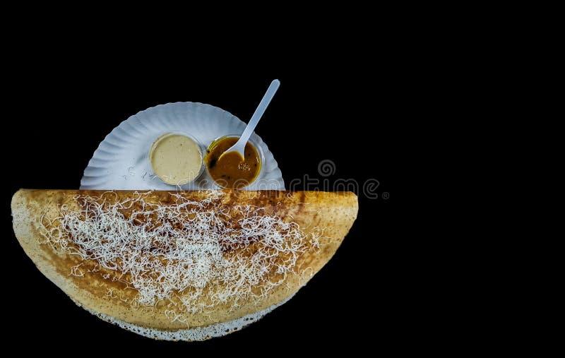 Dosa för lökostslätt med sambaren och chutney på svart bakgrund arkivfoton