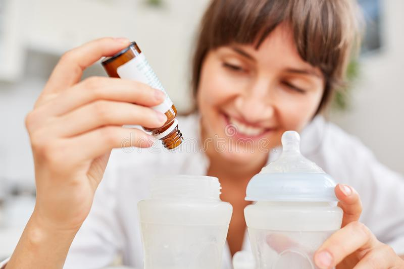 Dosage drops for abdominal pain. Mother dosed the drops for abdominal pain into the baby food royalty free stock photo