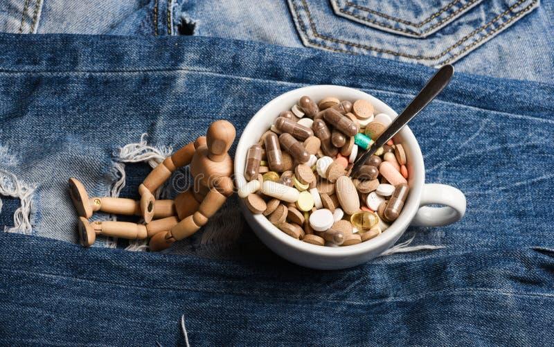 Dose de médecines Simulacre humain en bois près de pleins pilules et comprimés de tasse Cocktail de vitamine Problème de santé So image libre de droits