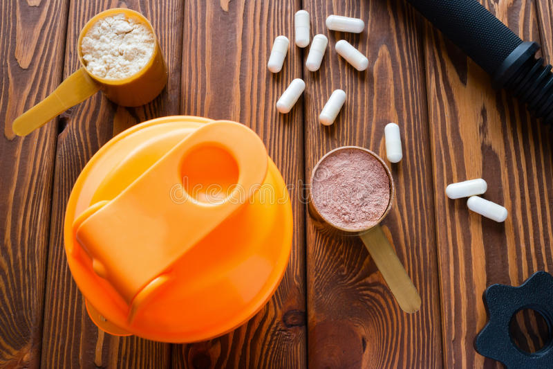Doseurs avec la protéine, les capsules d'acide aminé et le dumbbel photographie stock libre de droits