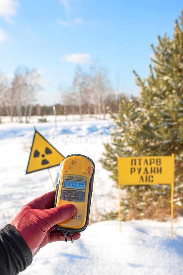 A dosimeter- radiometer in the hand of a tourist, shows a high level of radiation at the site of a burned forest during the. January 2019, Pripyat, Chernobyl stock images
